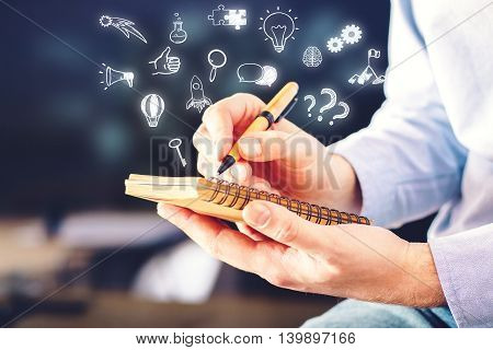 Businessman holding spiral notepad with abstract business icons on blurry background