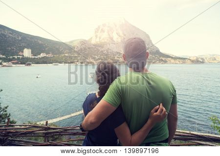 Embracing man and girl looking to hte mountain and harbour - vintage color.