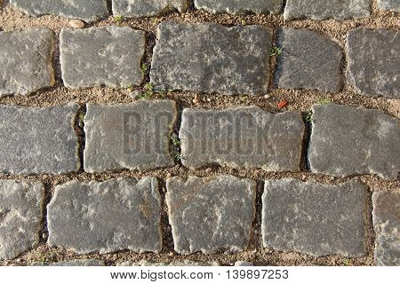very old cobble stones in roadway on the street top view / fragment old road