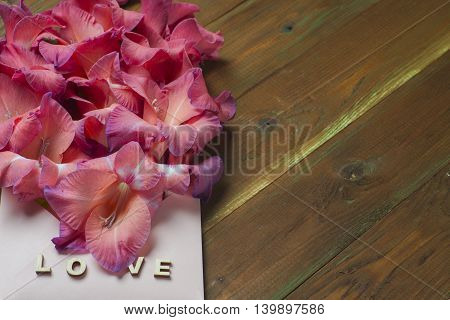 Colorful Flowers In Envelope, The Word Love, On Wooden Table, Delivery Concept. Congratulate