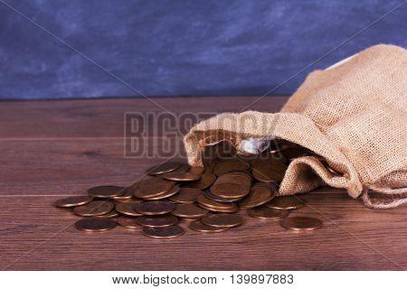 Bag Of Coins Spilt Over A Wooden Surface