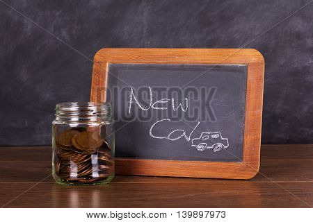 Glass Jar With Blackboard On Wooden Surface