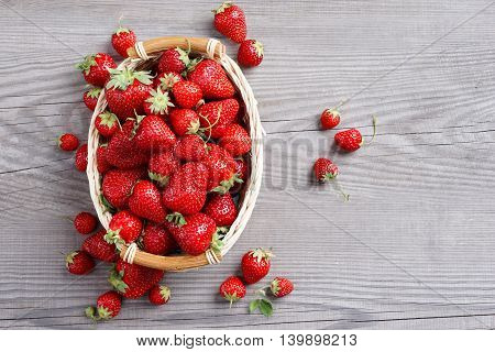 Deluxe strawberries in basket on wooden table. Close up top view high resolution product
