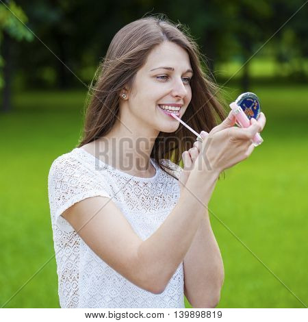 Assistant lipstick beautiful young brunette woman close up, summer outdoors