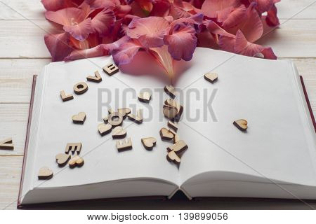 The Word Love A Lot Of Hearts, Flowers On A Background Of Book On A Wooden Table. Back To School Cop
