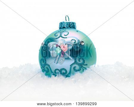 Turquoise Christmas balls in snow. Isolated.