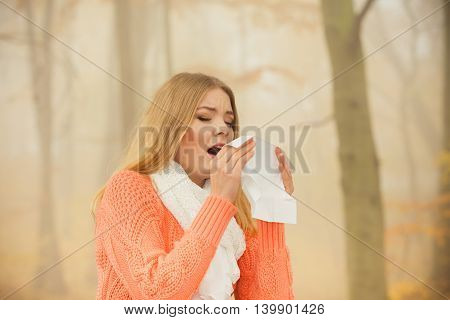 Sick woman in fall autumn park sneezing in tissue. Ill girl caught cold flu outdoor. Rhinitis or allergy. Health care.