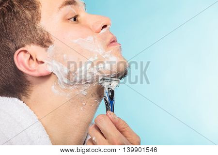 Young man shaving using razor with cream foam. Handsome guy removing face beard hair. Skin care and hygiene.