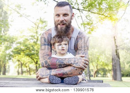 Tattooed Father Have Fun With His Son In The Park