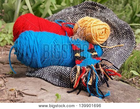 A basket of colorful cotton and acrylic yarns and small hand-woven tapestry in a natural outdoor setting.