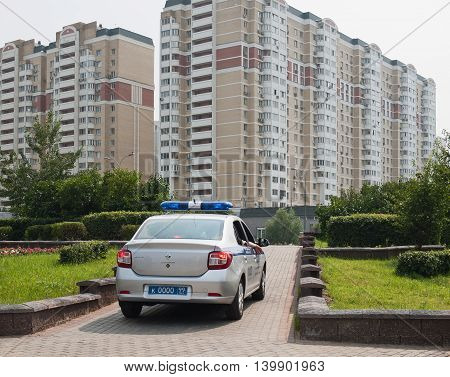 July 2016, Moscow, Russia. Police car in the background of the new district. On Board car phone stand part