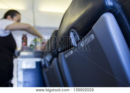 inside airplane close-up of seat with catering girl on background