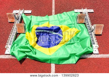 Brazilian flag on athletic track start grid with blocks - Close up of red running field with national symbol - Concept of international sport event and competitions - soft vignetting effect filter