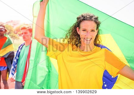 Brazilian woman sport fan holding flag at stadium with american and jamaican athletes background - Cheerful supporter girl with blonde curly hair looking camera - Concept of competition victory