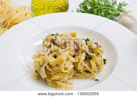 dish with tagliatelle and mushrooms and fresh ingredients on white wood