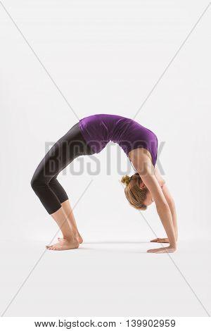 Sporty woman doing yoga exercise, showing urdhva dhanurasana, upward bow