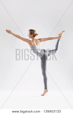 Sporty attractive beautiful woman doing yoga on a studio background