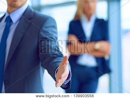 Young businessman ready to handshake standing in office