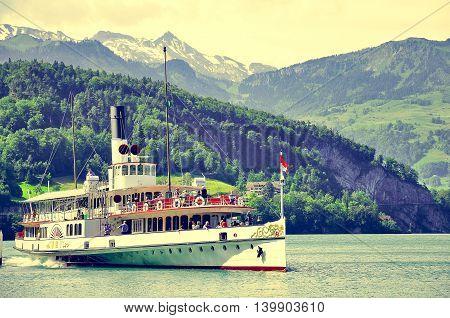 Vitznau Switzerland - June 10 2010: The passenger tourist steam boat leaving pier in central Switzerland.