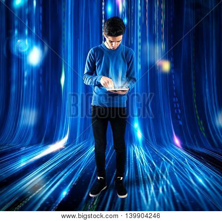 Boy touches the screen of a tablet with background lights