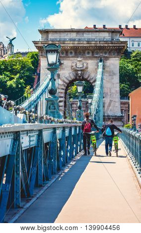 Tourists people with bicycles walking by chain bridge on danube river in budapest city hungary