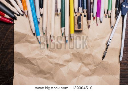 Closeup of crumpled brown paper colorful pencils compasses and sharpener. Mock up