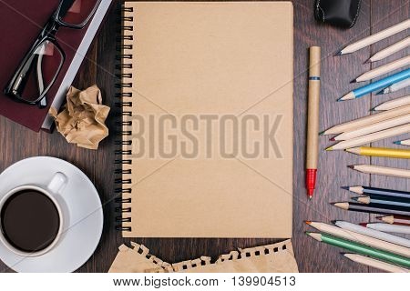 Top view of wooden desktop with brown paper spiral notepad coffee cup glasses and colorful pencils. Mock up