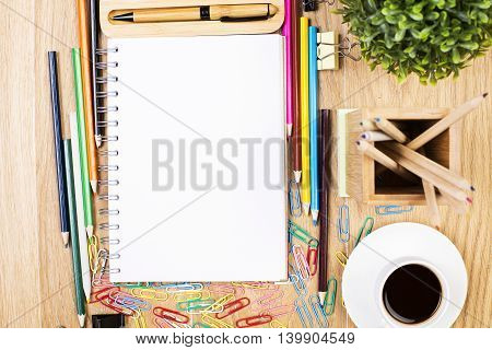 Wooden desktop with blank spiral notepad colorful supplies plant and coffee cup. Mock up