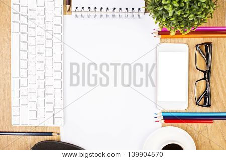 Closeup of wooden desktop with blank paper sheet coffee cup white smartphone glasses colorful pencils keyboard spiral notepad and decorative plant. Mock up