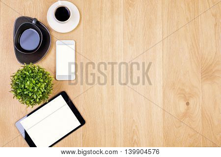 Top view of wooden desktop with blank white tablet smartphone coffee cups and decorative plant. Mock up