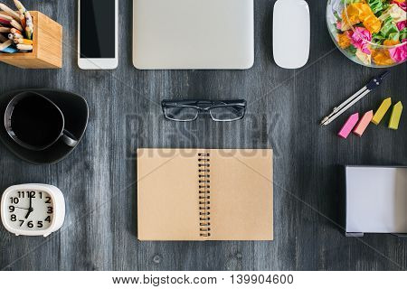Top view of dark wooden desktop with open spiral notepad blank smartphone closed laptop computer mouse glasses clock coffee cup and supplies. Mock up