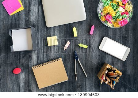 Top view of creative dark wooden desktop with blank white smartphone closed laptop and various colorful stationery items. Mock up