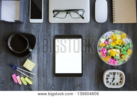 Top view of wooden office desktop with blank white pad smartphone coffee cup stationery clock closed laptop computer mouse and other items. Mock up