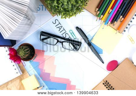 Top view and closeup of messy office desktop with glasses business report cactus open book and stationery items