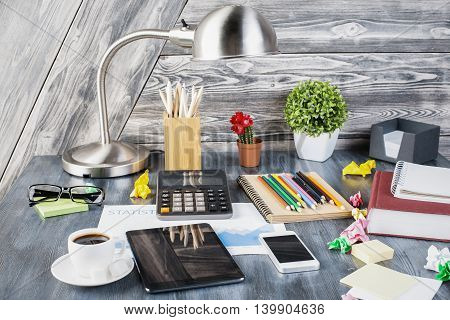 Closeup of creative messy desktop with blank tablet smartphone calculator table lamp decorative plants glasses various stationery items and other objects on wooden plank background. Mock up