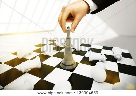 Businessman playing chess on interior background. Strategic planning concept