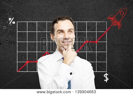 Start up concept with happy thoughtful businessman. Business chart with red rocket ship on concrete wall in the background