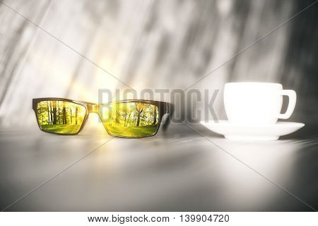 Blurry grey table with coffee cup and green forest reflected on glasses lens