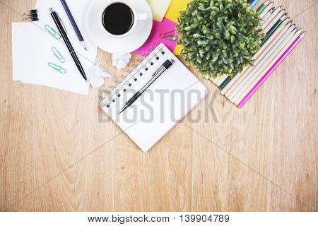 Top view of wooden office desktop with coffee cup plant and various stationery items