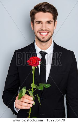 Handsome Businessman With Beaming Smile Holding Red Rose