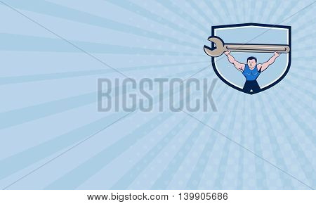 Business card showing illustration of a mechanic lifting giant spanner wrench over head viewed from front set inside shield crest on isolated background done in cartoon style.