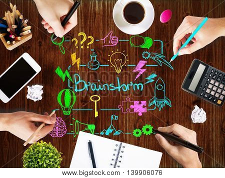Brainstorm concept with businesspeople hands drawing sketch on wooden office table with blank smartphone coffee cup stationery and other items