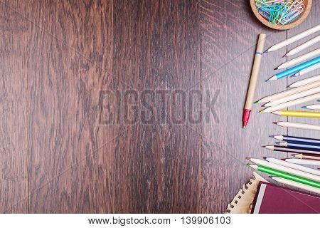 Closeup of blank wooden desktop with colorful pencils and paper clips on its right side. Top view