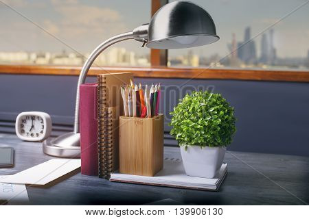 Closeup of table lamp notepads book pencil holder clock and plant on dark wooden office desktop. Window with city view in the background