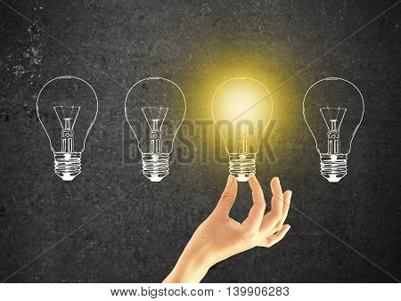 Idea concept with female hand holding abstract illuminated light bulb on dark concrete background