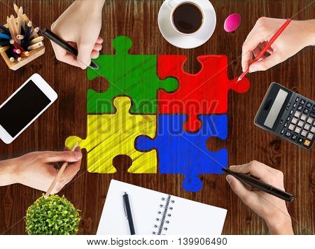 Teamwork and partnership concept with businessmen's hands drawing colorful puzzle pieces on wooden office desktop with blank cellphone coffee cup calculator notepad and other items