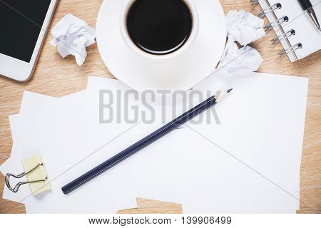 Messy office desktop with paperwork coffee cup and smartphone