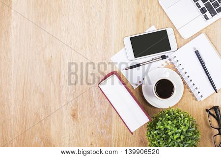 Wooden desktop with blank smartphone coffee cup laptop keyboard book plant glasses paper sheets and pens. Mock up