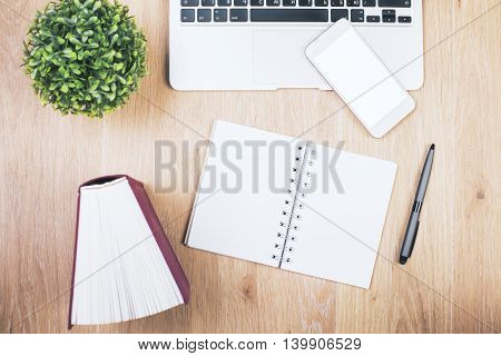 Closeup of light wooden desktop with blank spiral notepad hardcover book pen decorative plant white cellphone and laptop keyabord. Mock up