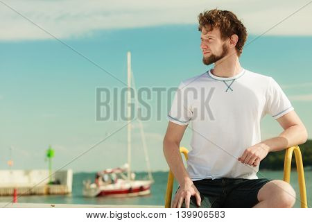 Fashion young man guy relaxing enjoying summer sunny day outdoor. Vacation holiday.